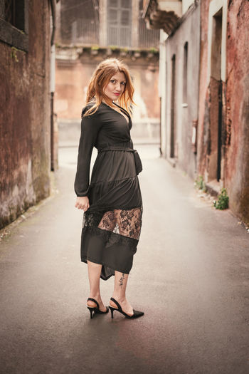 Portait of an attractive woman outdoor looking at camera Women Full Length One Person Architecture Portrait Young Adult Adult Looking At Camera Beautiful Woman Standing Young Women Built Structure Hairstyle Fashion Clothing Beauty Direction Focus On Foreground Hair Dark Blackandwhite Antique Ancient Urban Outdoors Attractive Woman Females