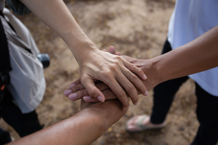 High angle view of friends stacking hands outdoors