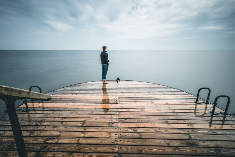 Man standing on pier by sea against sky