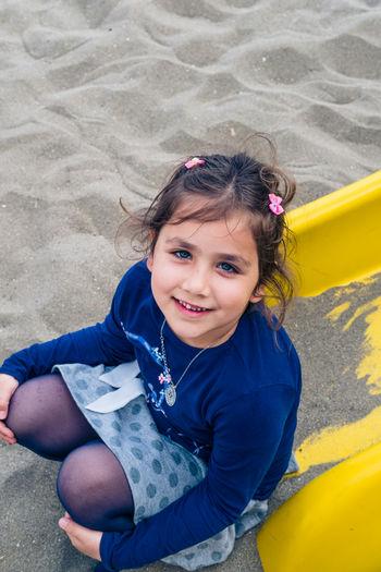 High Angle Portrait Of Girl Sliding At Playground