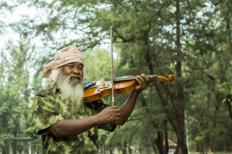 Portrait of bearded man playing violin against trees