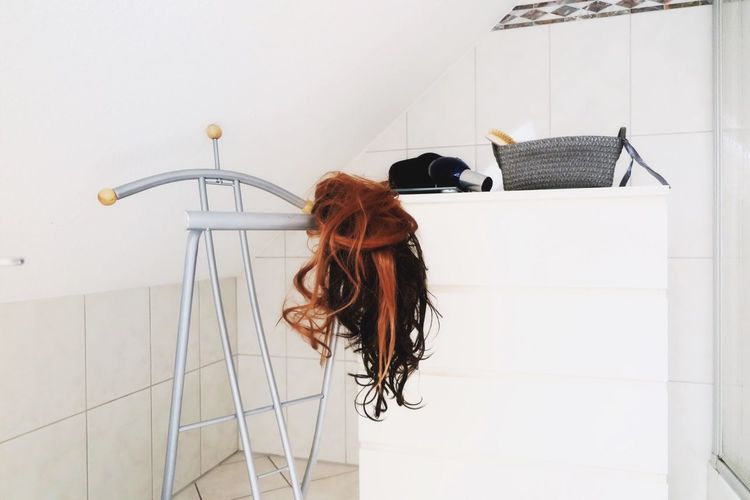 Brown wig on rack by hair dryer and bag on table in room