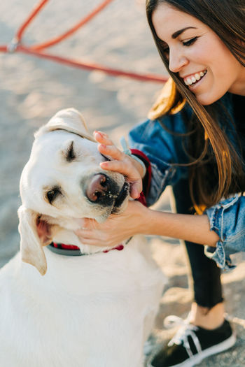 Cheerful Woman Petting Dog At Playground During Sunset