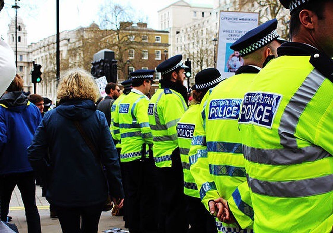 police force, large group of people, men, adult, togetherness, uniform, police uniform, city, building exterior, standing, riot, day, outdoors, match - sport, people, adults only, reflective clothing