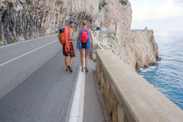 Couple with backpacks walking on road by sea