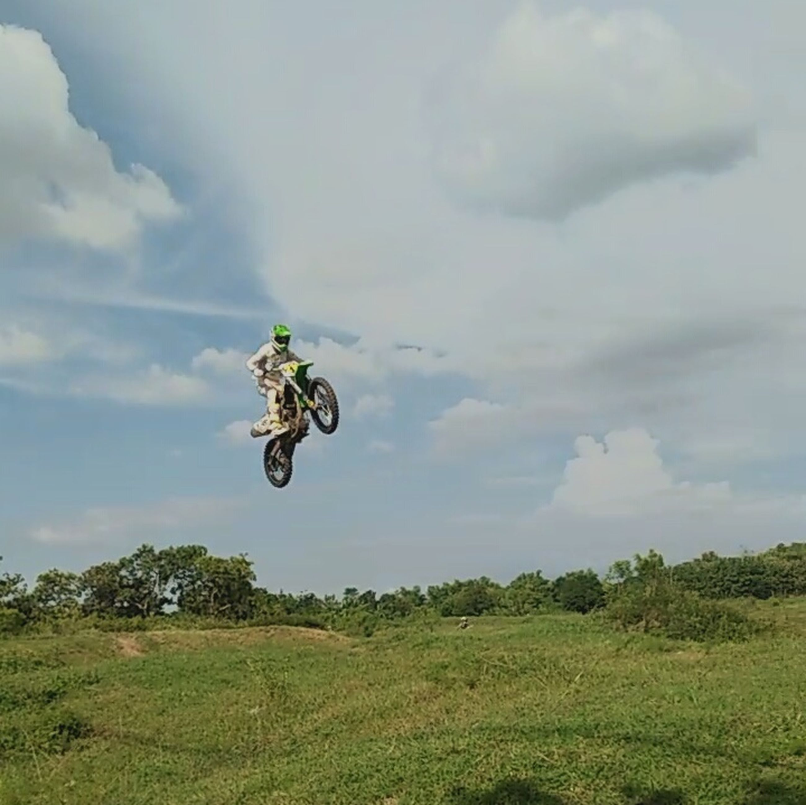 mid-air, cloud - sky, skill, low angle view, sport, full length, outdoors, sky, one person, motocross, leisure activity, stunt, headwear, extreme sports, tree, day, people, competitive sport, motorsport, drone, adult