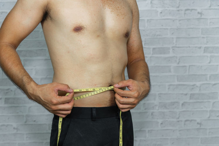 Midsection of shirtless man measuring waist with tape measure by wall