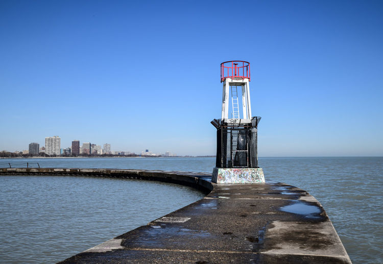 Warning light by sea against clear blue sky