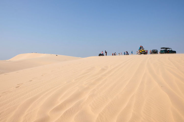 Low Angle View Of People With Vehicles On Sand Dune In Desert Against Blue Sky