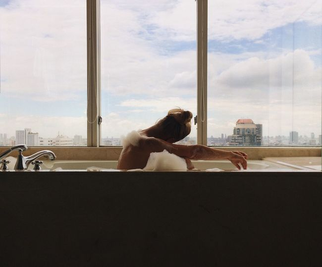 Bath Relaxing Bathtub Chilling Staycation Window Sky Cloud - Sky One Person Built Structure Day Real People Hotel Luxury Looking Through Window Architecture Indoors  Women Lifestyles City Sitting Building Exterior One Young Woman Only Cityscape One Woman Only