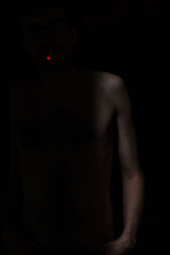 Low section of man standing against black background