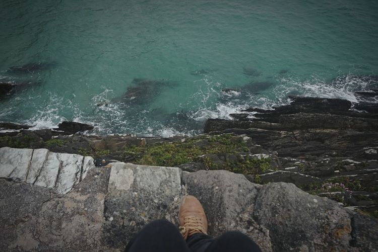 Low section of man standing on rock by sea