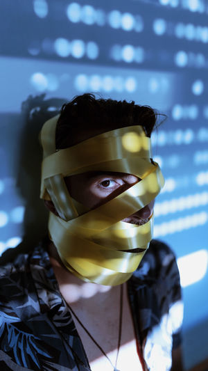 Close-up portrait of man with yellow adhesive tape rolled on face against wall