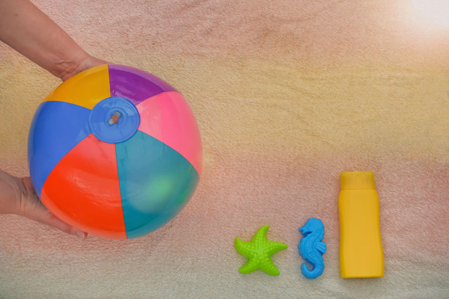 Sunny summer holidays - background Copy Space Hands Holiday Recreation  Summer Holidays Background Ball Beach Holiday Beach Towel Bottle Concept Crème High Angle View Holding Human Body Part Human Hand Lens Flares School Holidays Sea Horse Starfish  Summer Towel Toy Water Polo Yellow