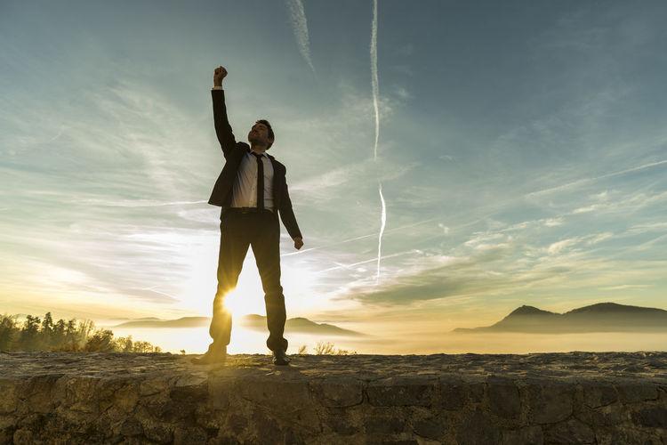 Full length of man standing against sky during sunset