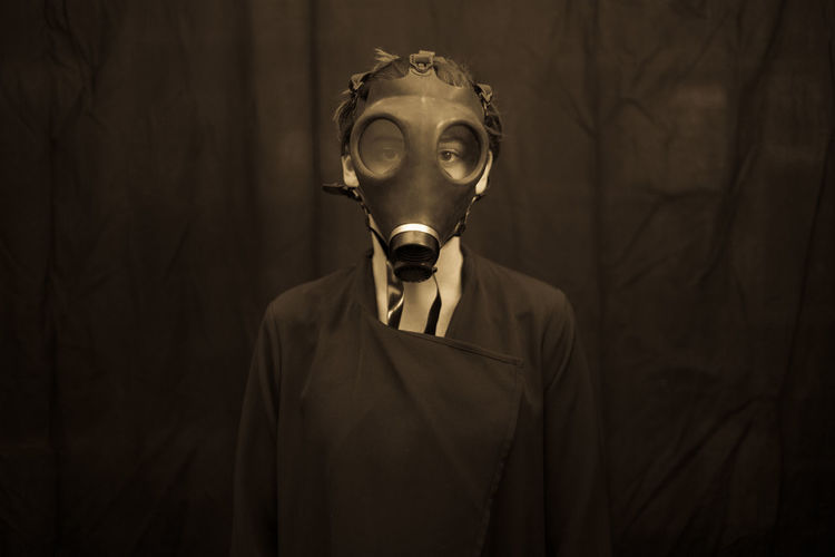 Portrait Of Young Woman Wearing Gas Mask
