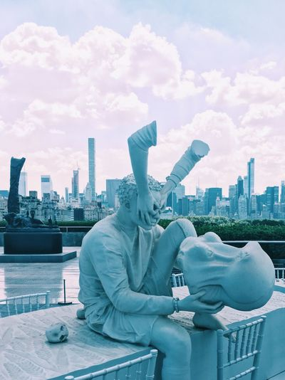 Statue in city against cloudy sky