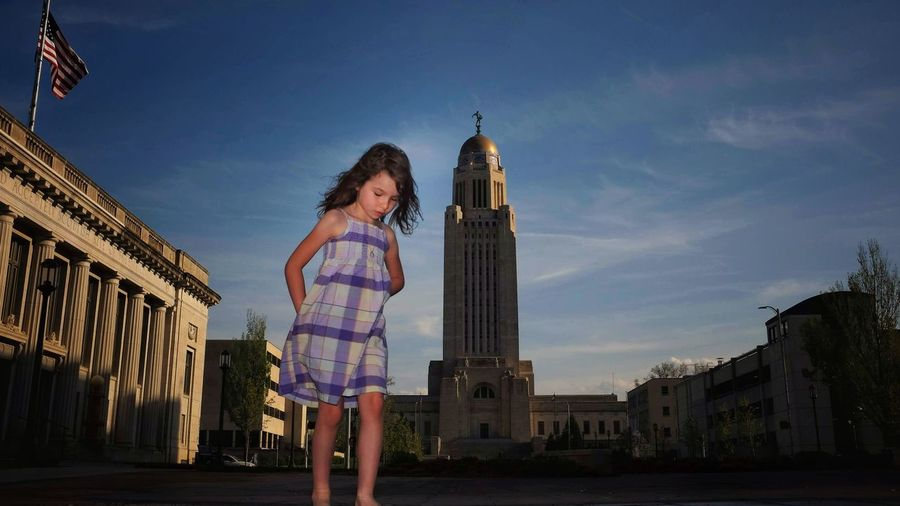 Girl standing against nebraska state capitol building