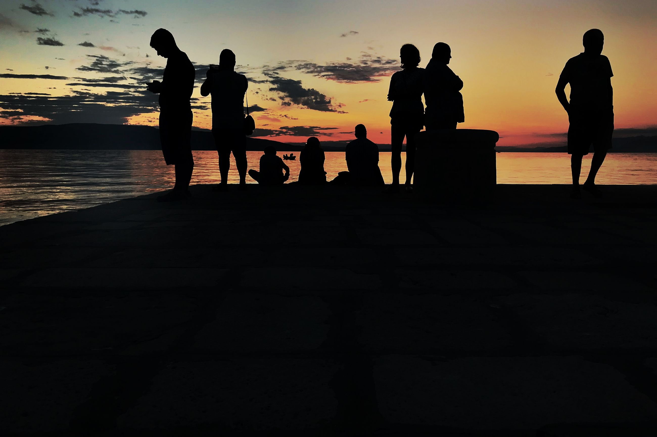 silhouette, sunset, water, sky, group of people, sea, beach, real people, beauty in nature, scenics - nature, lifestyles, land, leisure activity, men, nature, people, standing, orange color, women, horizon over water, outdoors