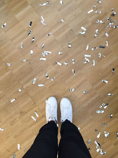 Low Section Of Person Standing By Confetti On Hardwood Floor