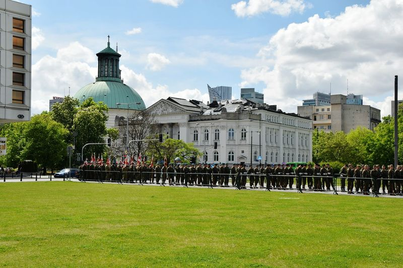 Army soldiers on lawn in front of church against sky