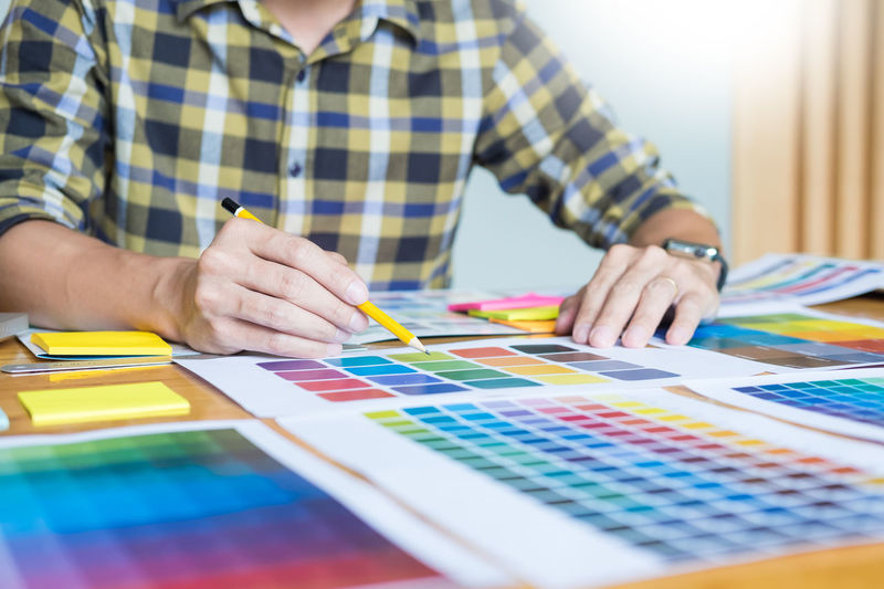 Midsection of man drawing on color swatches at office