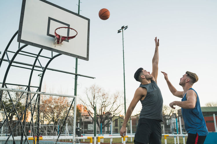 Young men playing basketball against sky