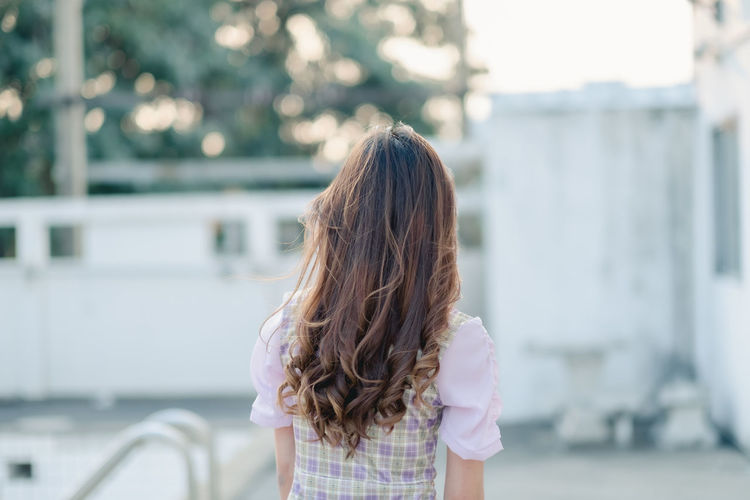 Rear view of woman standing against blurred background