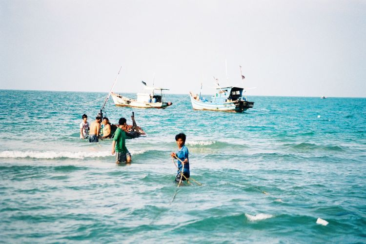 People fishing in sea against clear sky