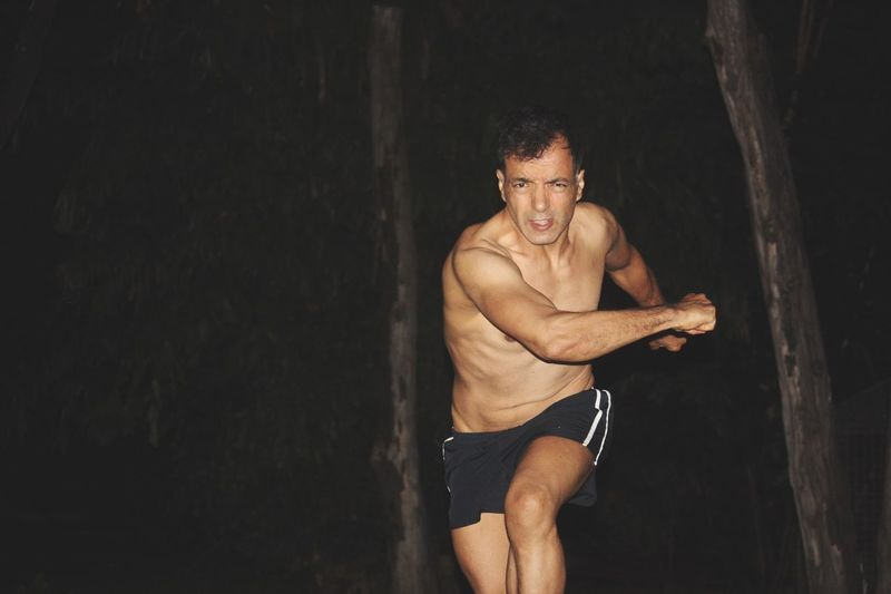 Portrait of shirtless man running against trees