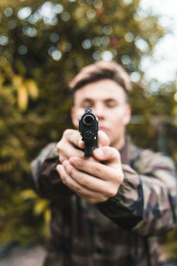Man shooting gun while standing outdoors