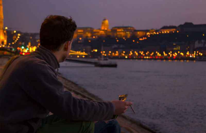 Man Smoking While Sitting At Lakeshore Against Illuminated City