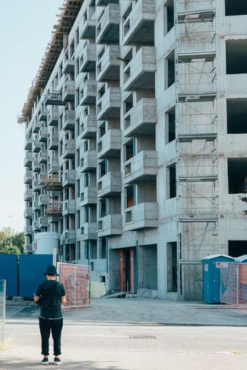 Rear View Of Man Standing On Street Against Buildings