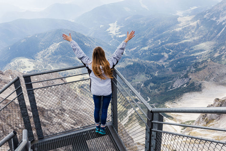 Woman standing by railing with mountains in background
