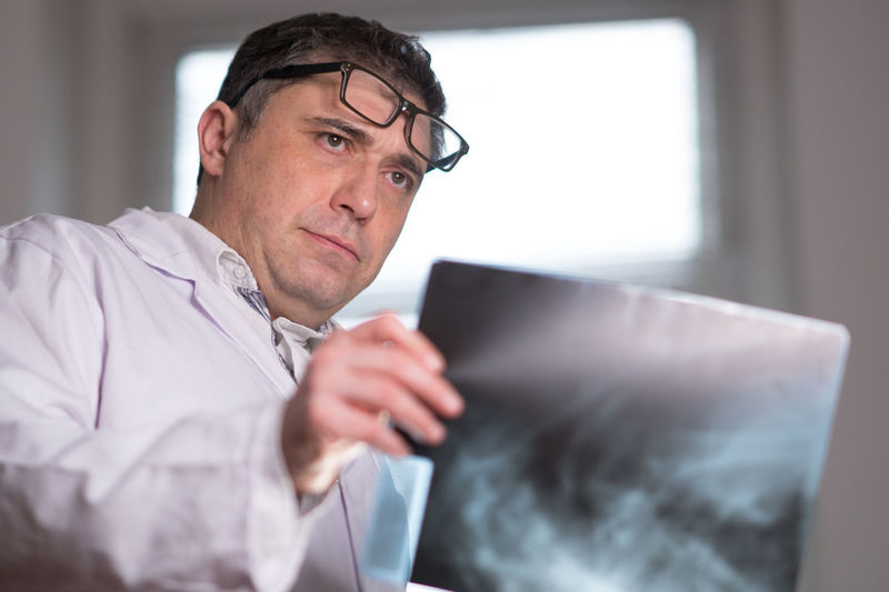 Doctor wearing a white lab coat examining X-ray images Broken Bones Diagnosis Doctor  Hospital Medicine Radiology Department Skeleton X Rays X-Rays Xray Anatomy Clinic Diagnostic Doctors Examining General Practitioner Healthcare And Medicine Lab Coat Medical Orthopedics Radiologist Radiology X Ray X-Ray Xrays