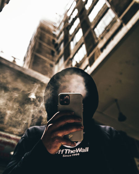Portrait of man photographing camera on mobile phone