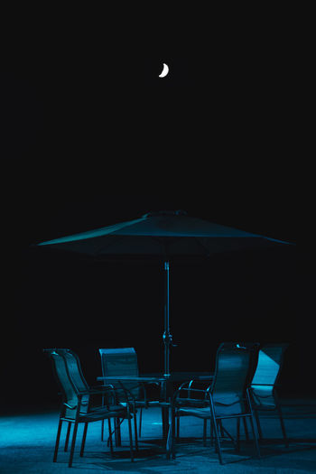Empty chairs and tables at night
