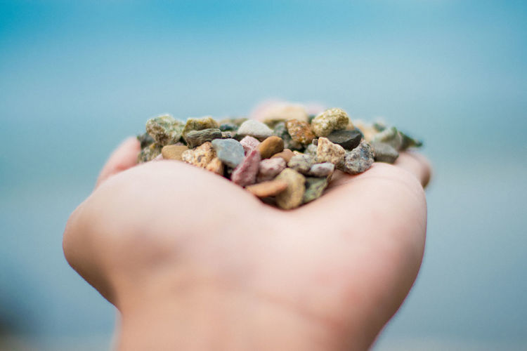 Cropped Image Of Hand Holding Small Stones