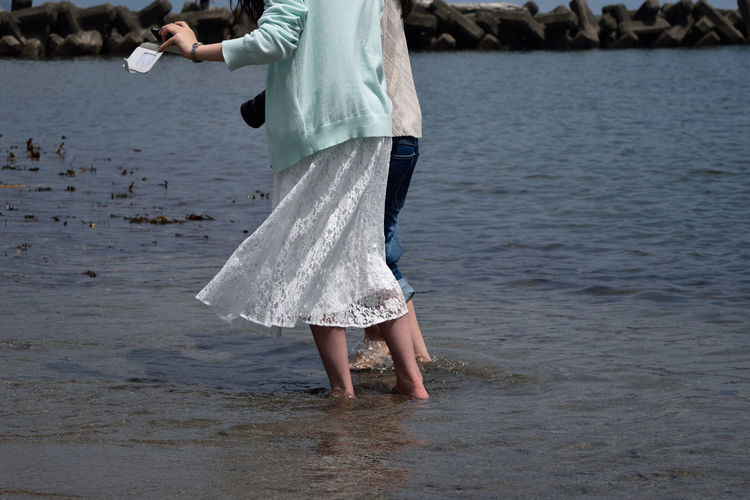 Midsection of friends wading in sea