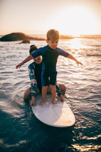 Boys Child Males  Childhood Water Men Two People Leisure Activity Full Length Togetherness Family Real People Sea Lifestyles Sunset Nature People Son Positive Emotion Innocence Surfing Teaching