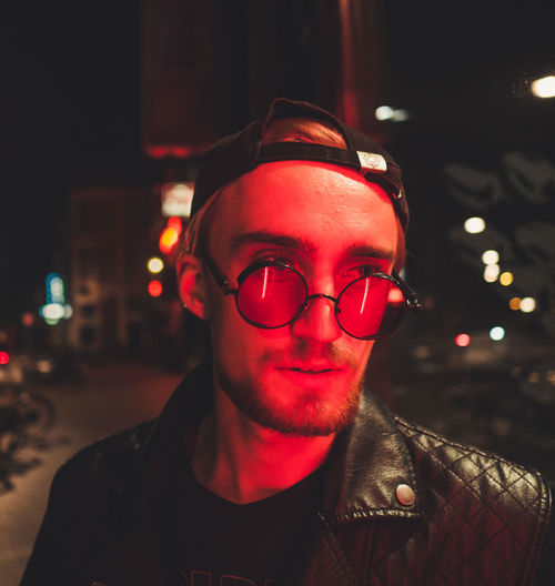 Young Man Wearing Eyeglasses In Illuminated City At Night