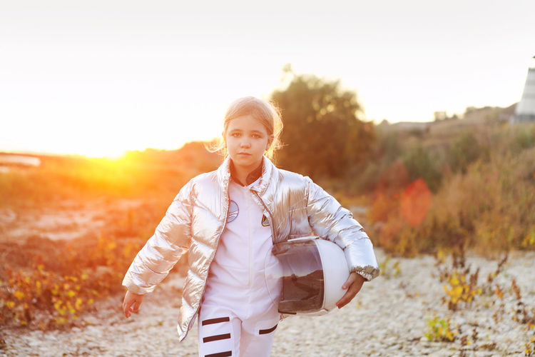 Portrait of teenage girl standing on field