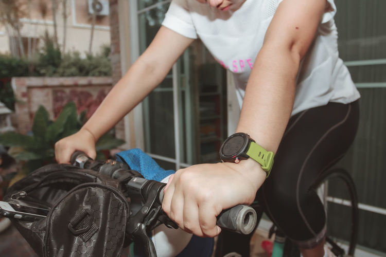 Midsection of woman holding bicycle