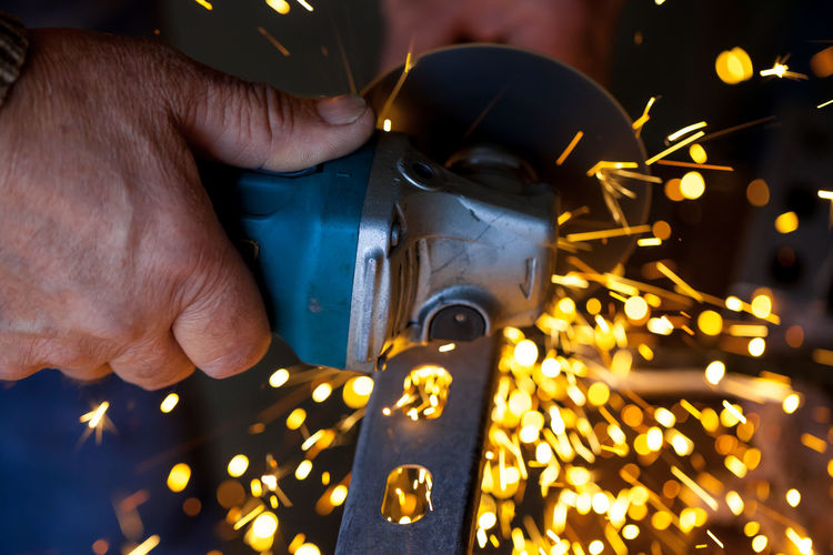 Cropped Image Of Worker Cutting Metal