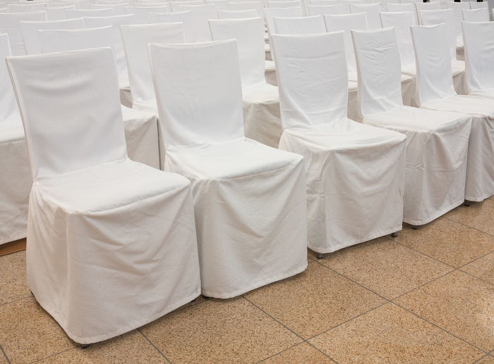 Chairs covered with fabric arranged in a row