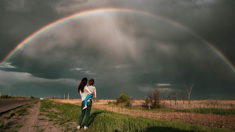 Rear view of woman standing against rainbow in sky