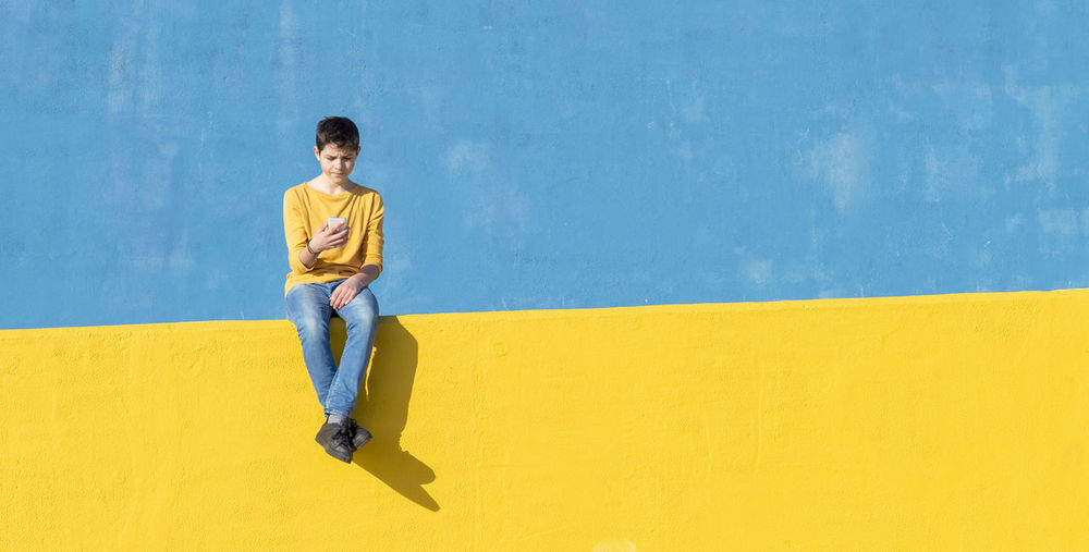 Boy using phone while sitting on yellow railing against blue wall