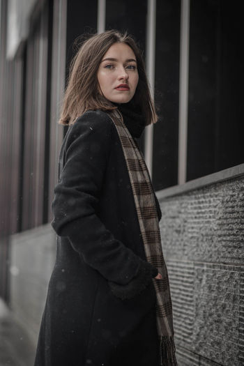 Portrait Of Young Woman In Warm Clothing Standing Against Building
