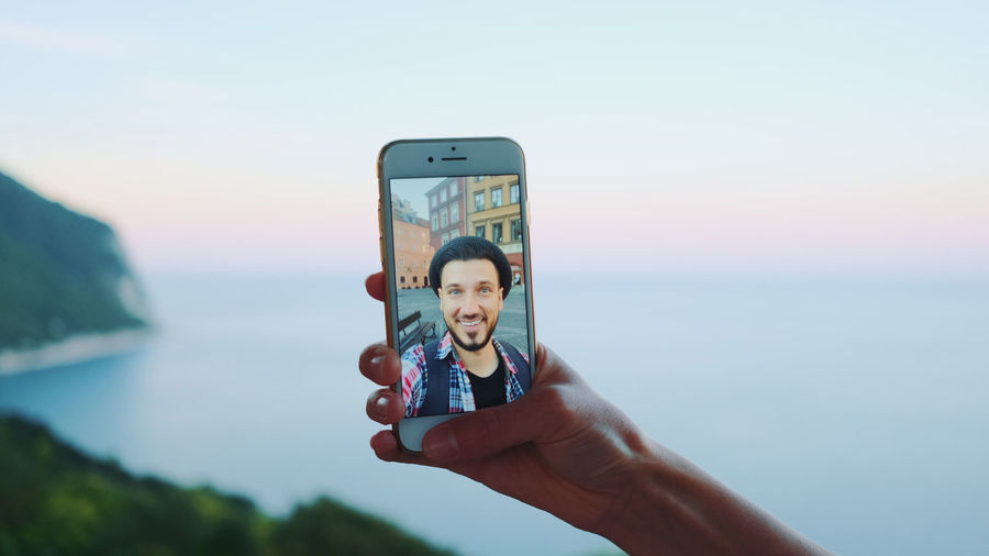 Cropped hand of woman holding mobile phone with man photo