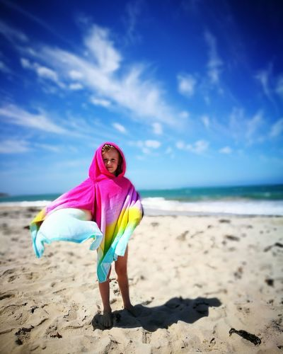 Boy Covered With Towel While Standing At Beach Against Sky